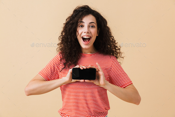 Emotional excited young curly woman showing display by mobile phone. Looking camera. - Stock Photo - Images
