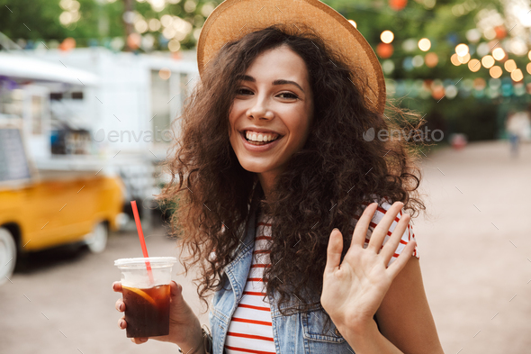 Image of stylish pretty woman 18-20 with curly brown hair wearin - Stock Photo - Images