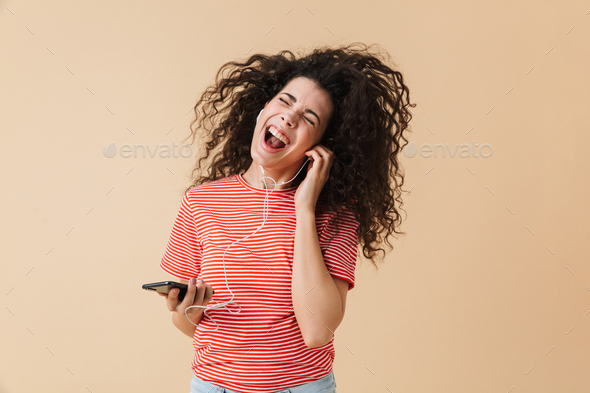 Emotional happy excited young curly woman listening music - Stock Photo - Images