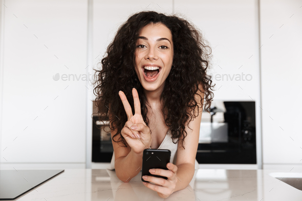 Beautiful happy woman 20s with curly brown hair wearing silk lei - Stock Photo - Images