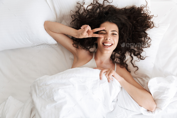 Image from top of happy woman 20s with dark curly hair lying in - Stock Photo - Images