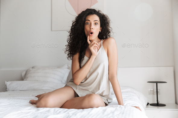 Image of excited curly woman sitting on bed with white linen at - Stock Photo - Images