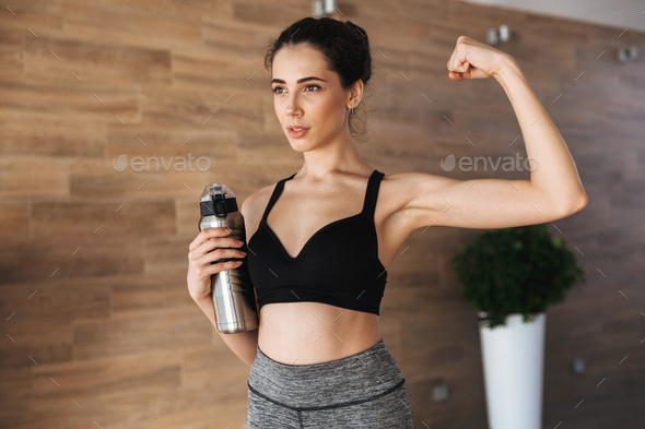 Strong young sportswoman holding water bottle - Stock Photo - Images