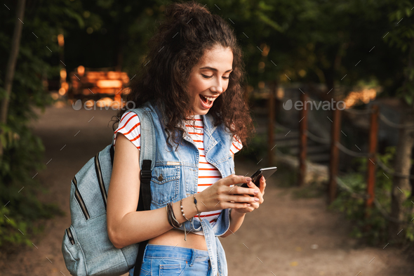 Photo of young delighted woman 18-20 wearing backpack, smiling a - Stock Photo - Images
