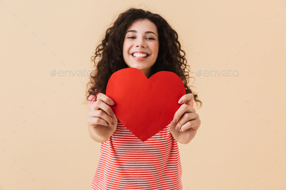 Smiling lovely girl showing big paper heart - Stock Photo - Images