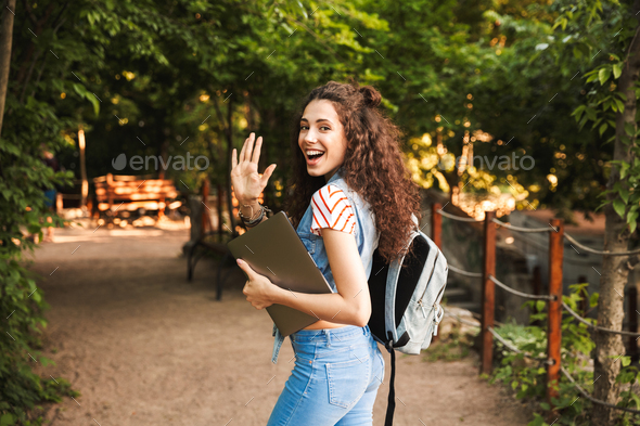 Portrait of friendly attractive woman 18-20 wearing backpack, wa Stock Photo by vadymvdrobot