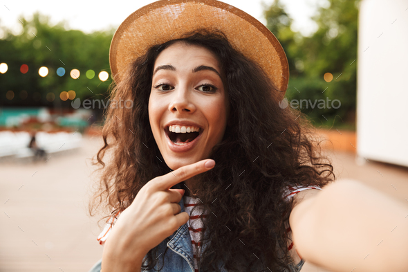 Cheerful happy woman 18-20 with curly brown hair, smiling and po - Stock Photo - Images