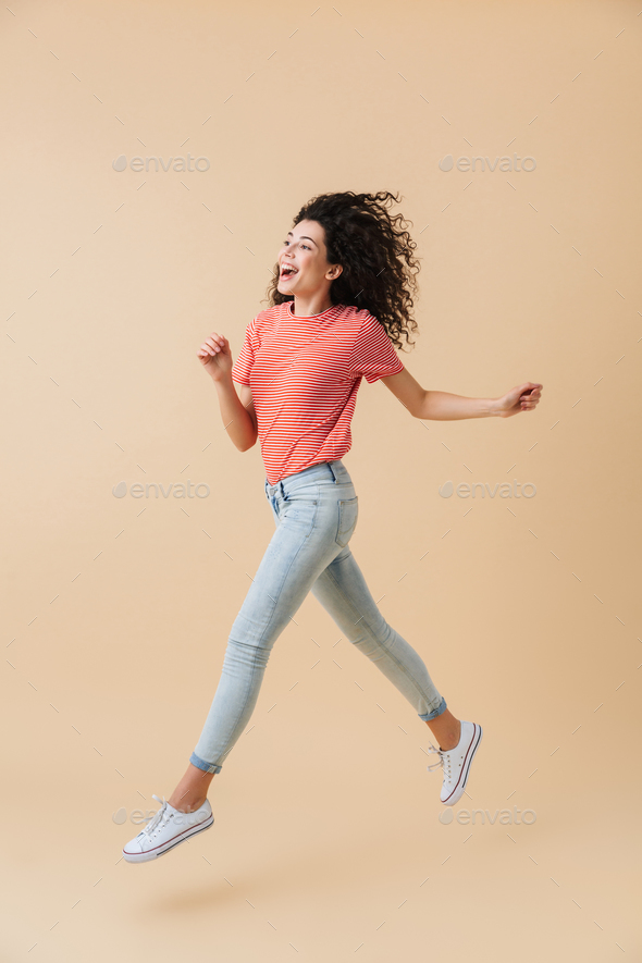 Woman jumping isolated over beige wall background. - Stock Photo - Images