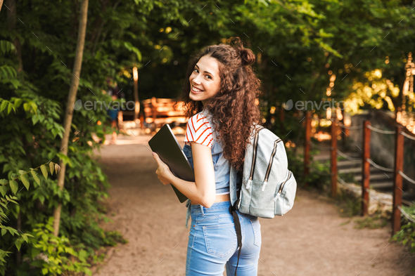 Photo of smiling caucasian woman 18-20 wearing backpack, walking - Stock Photo - Images