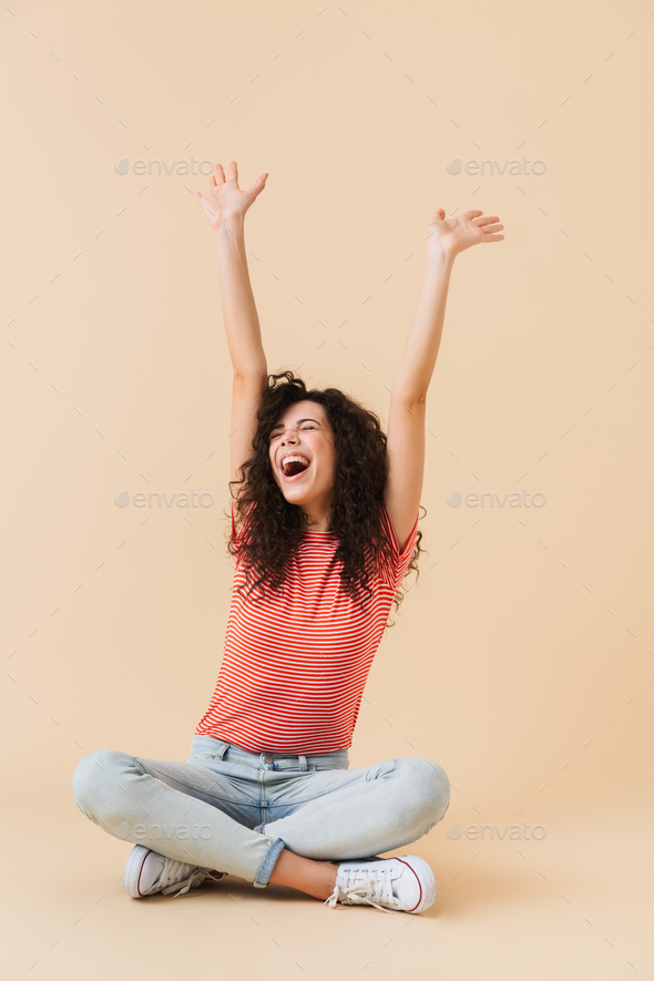 Screaming happy young woman sitting isolated - Stock Photo - Images