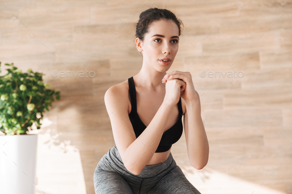 Confident young sportwoman doing squats - Stock Photo - Images