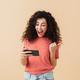 Young curly woman play games by mobile phone. - PhotoDune Item for Sale