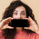 Cute young curly woman showing display by mobile phone covering mouth. - PhotoDune Item for Sale