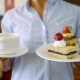 Shot of a Woman Holding Two Plates with Dessert and Cup of Coffee for Breakfast - VideoHive Item for Sale