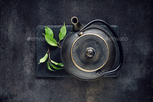 Green tea leaf with black teapot - Stock Photo - Images