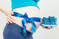 Pregnant woman with baby booties and blue ribbon, concept of expecting for newborn - PhotoDune Item for Sale