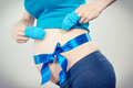 Pregnant woman with baby gloves and blue ribbon, concept of expecting for newborn - PhotoDune Item for Sale