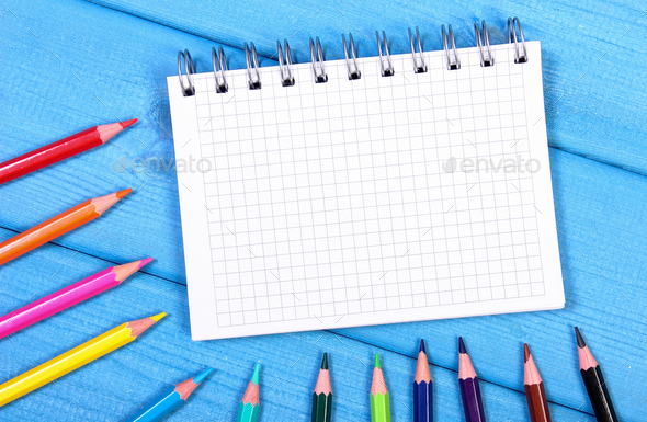 Colorful crayons and notepad on boards, school accessories, copy space for text - Stock Photo - Images