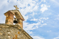Old stone orthodox church and bell on blue sky, in Greece.