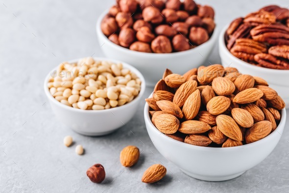 Almonds, pecans, pine nuts and hazelnuts in white bowls on grey background. Nuts mix. - Stock Photo - Images