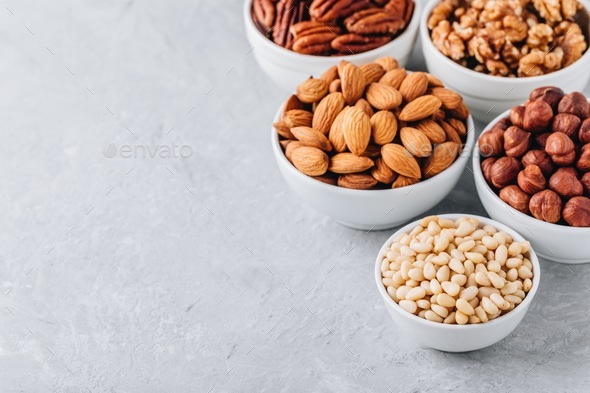 Pine nuts, almonds, pecans, walnuts and hazelnuts in white bowls on grey background.  - Stock Photo - Images