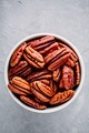 Raw pecan nuts in bowl on gray background. - PhotoDune Item for Sale
