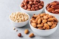 Almonds, pecans, pine nuts and hazelnuts in white bowls on grey background. Nuts mix. - PhotoDune Item for Sale