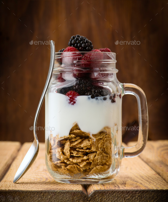 jug with berries cerealas  and yogurt on wood - Stock Photo - Images