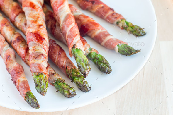 Green asparagus wrapped with bacon on white plate, horizontal - Stock Photo - Images
