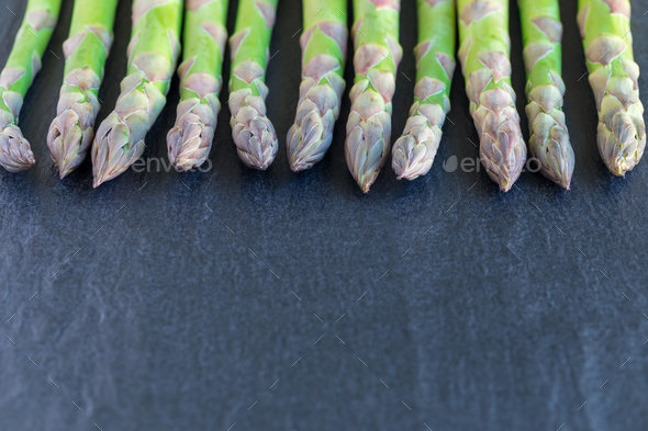 Bunch of fresh green asparagus on dark slate background, horizon - Stock Photo - Images