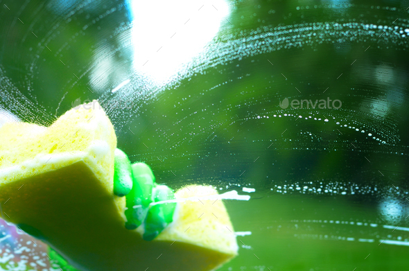 Male hand in green glove with yellow sponge washing car window - Stock Photo - Images