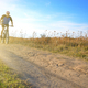 Male cyclist driving by rural dirt road outdoors - PhotoDune Item for Sale