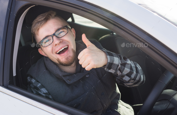 Cheerful casual guy smiling happily showing thumbs up sitting in a big white car - Stock Photo - Images