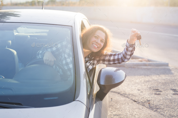 Young smiling girl sitting behind the wheel of a car and holding key in his hand - Stock Photo - Images