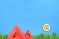 Conceptual summer landscape with watermelon, lemon and green leaves on blue table - PhotoDune Item for Sale