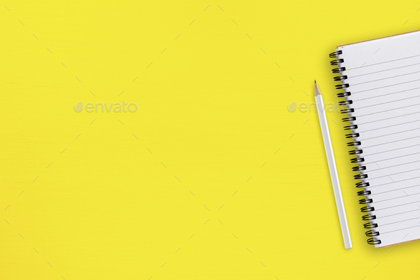 Pencil and notepad on yellow table top view - Stock Photo - Images
