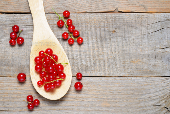 Red currant in wooden spoon on table - Stock Photo - Images