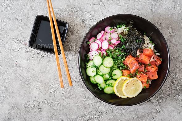 Hawaiian salmon fish poke bowl with rice, radish,cucumber, tomato, sesame seeds and seaweeds. - Stock Photo - Images