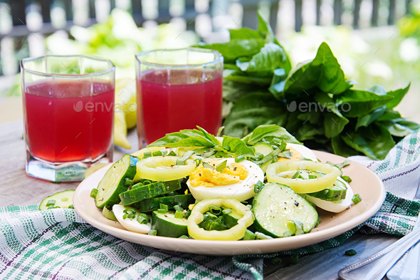 Breakfast in the summer garden. Salad of eggs and cucumbers with green onions and basil. - Stock Photo - Images