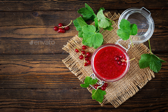 Red currant jam in a jar on a wooden background. Tasty food. Flat lay. Top view - Stock Photo - Images