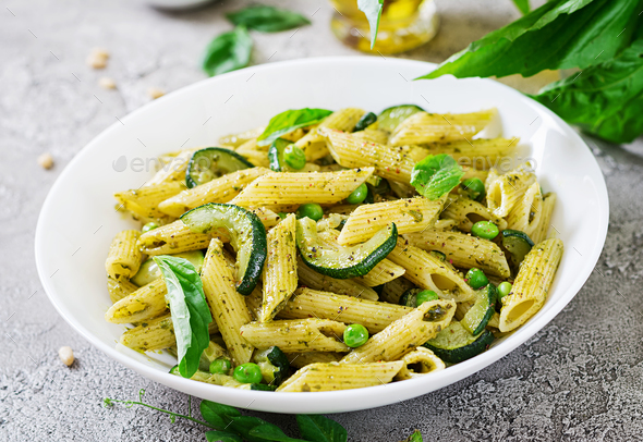 Penne pasta with  pesto sauce, zucchini, green peas and basil. Italian food. - Stock Photo - Images