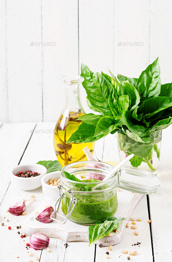 Homemade pesto sauce fresh basil, pine nuts and garlic on white wooden background. Italian food. - Stock Photo - Images
