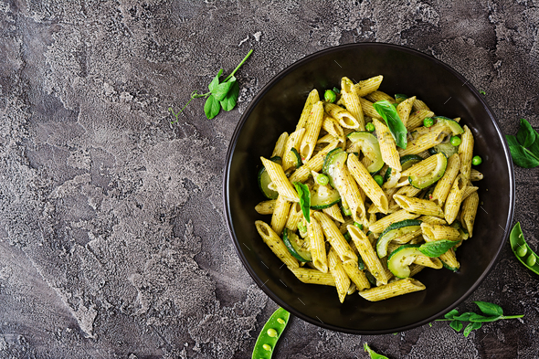 Penne pasta with  pesto sauce, zucchini, green peas and basil. Italian food. Top view. Flat lay. - Stock Photo - Images