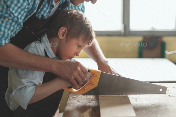 Father and son sawing a plank - Stock Photo - Images