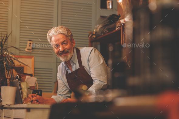 Smiling elderly man at work - Stock Photo - Images