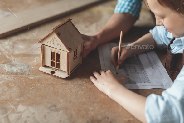 Little boy with a wooden house - Stock Photo - Images