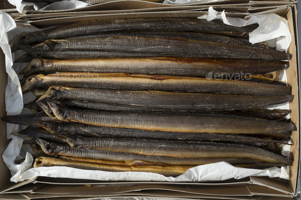 Fresh smoked eels in a cardboard box - Stock Photo - Images