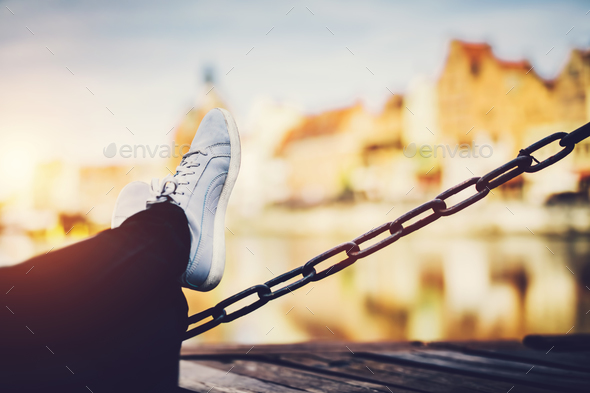 Girl's legs leaning on a chain, a river and old buildings in background - Stock Photo - Images