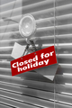 """Sign saying """"Closed for holiday"""" on a glass door"""
