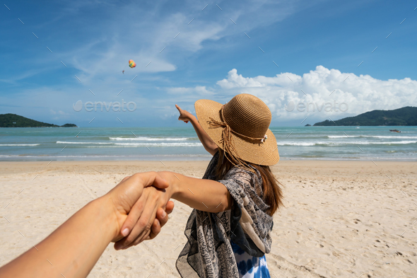 Young woman traveler holding man's hand and looking parachute flying in the sky on the beach - Stock Photo - Images
